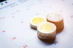 泰铢在一本打印的日历的金钱堆特写镜头与在黑和红色的数字在黑背景 金钱savi的概念 图库摄影