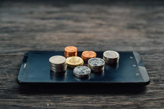 泰铢硬币和金钱在巧妙的电话 免版税库存图片