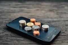 泰铢硬币和金钱在巧妙的电话 免版税库存照片