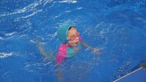 泳装、盖帽和风镜的女孩是潜水和游泳对水池egge  影视素材