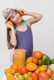 泳装和夏天帽子的女孩用做耳机的柑橘水果 库存照片