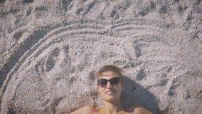 泳装和太阳镜的女孩在海滩说谎,微笑和做她的手圈子在沙子 股票录像