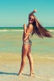 泳装和太阳镜的年轻美丽的女孩在海滩 免版税库存照片