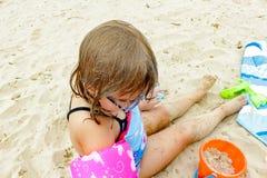 泳装和帽子的可爱的女孩在热带海滩 免版税图库摄影