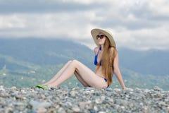 泳装和帽子的美丽的女孩坐在山和天空背景的一个小卵石  免版税库存图片