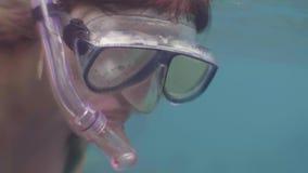 泳装和废气管面具游泳的年轻女人在水下在蓝色海 潜航在海洋水中的妇女 ?? 影视素材