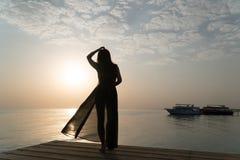 泳装和斗篷的一个女孩在码头站立并且遇见黎明 免版税库存照片