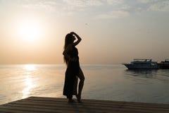 泳装和斗篷的一个女孩在码头站立并且遇见黎明 库存照片
