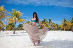 泳装和流动的裙子的年轻女人,跳舞在一个加勒比海滩 库存照片