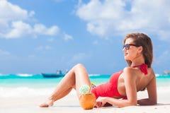 泳装和草帽的少妇在太阳镜用在海滩的椰子 免版税图库摄影