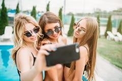泳装广告太阳镜的三个女孩做selfie 免版税库存照片
