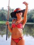 泳装的一个女孩在有被抓的一根钓鱼竿和鱼的一个帐篷 免版税图库摄影
