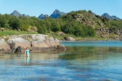 泳装的一个女孩有一台照相机的在绿松石水, Lofoten,挪威中 免版税图库摄影