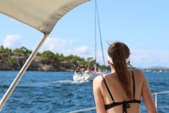 泳装的一个年轻苗条女孩坐船尾并且观看航行游艇通过  在水的一个豪华假日wea的 免版税图库摄影