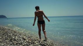泳装的一个苗条女孩,走沿与小卵石的海滩在蓝色海附近 HD, 1920x1080 慢的行动 股票视频