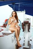 泳装的一名美丽的妇女坐游艇 库存照片