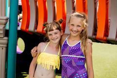 泳装的两个女孩获得在草的乐趣由水池 免版税图库摄影