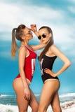 泳装的两个性感的夫人在海滩 库存照片