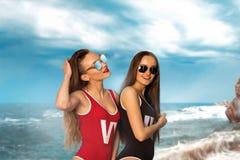 泳装的两个性感的夫人在海滩 免版税库存图片
