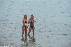 泳装的两个性感的女孩在水中的采取一selfie与智能手机 图库摄影