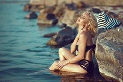 黑泳装的华美的被晒黑的性感的金发碧眼的女人坐在水中在大石头爱抚她的与闭合的眼睛的脖子 免版税库存图片