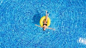 泳装的可爱的妇女在游泳池的黄色橡胶环从上面 免版税库存图片