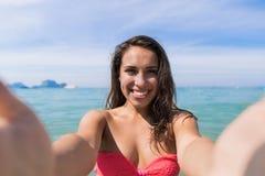 泳装的可爱的年轻白种人妇女在拍Selfie照片,女孩蓝色海水假日的海滩 库存照片