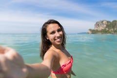 泳装的可爱的年轻白种人妇女在拍Selfie照片,女孩蓝色海水假日的海滩 图库摄影
