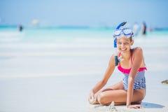 泳装的女孩和水肺掩没和获得乐趣坐热带海滩 免版税库存图片