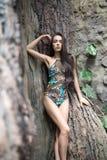 泳装的女孩在树附近 免版税库存照片