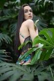 泳装的女孩在植物之间 免版税库存图片
