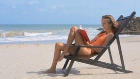 泳装的女孩晒黑读书反对海波浪 股票视频