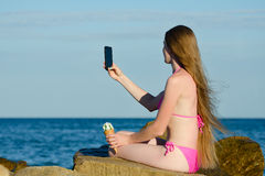 泳装的女孩有冰淇凌的在多岩石的海滩在手中做selfie电话反对海 库存图片