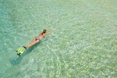 泳装的妇女游泳与废气管和飞翅在一蓝色wa 库存图片