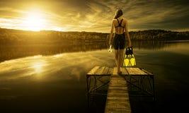 泳装的妇女潜水者,在码头边缘 图库摄影