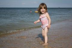 泳装的小孩坚持海和微笑 免版税库存照片