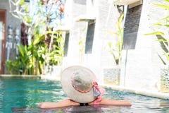 泳装的少妇在华美的手段,豪华别墅,热带巴厘岛,印度尼西亚的游泳池 免版税库存照片