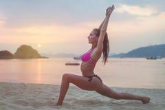泳装的少妇行使在海滩的舒展她的腿在日落期间海上 做锻炼的健身女孩  免版税库存图片