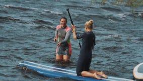 泳装的少妇击倒冲浪板入水,笑并且无所事事  股票录像