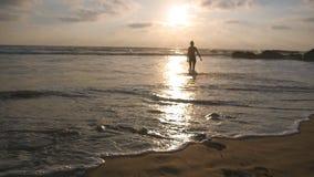 泳装的少妇继续海海滩沐浴在日落 走在岸的美丽的女孩到海洋在期间 股票视频