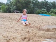 泳装的年轻十几岁的女孩坐沙子在海滩异乎寻常的手段 免版税库存图片