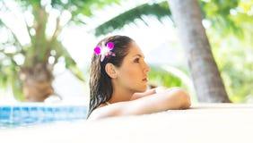泳装的年轻和运动的妇女 放松在水池的女孩在夏天 库存图片