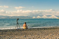 泳装的年轻在Rion-Antirion的女性在与三脚架的海滩和照相机在帕特雷,希腊附近跨接背景 免版税库存图片