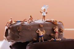 泳装的微型人在雪糕 库存图片