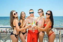 泳装的微笑的朋友在蓝色海背景 愉快的人民夏令时画象  放松在a的朋友 免版税库存照片