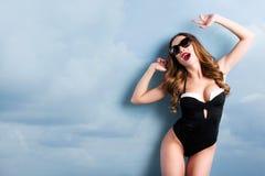 泳装的快乐的妇女在天空背景 夏天自由 免版税库存图片