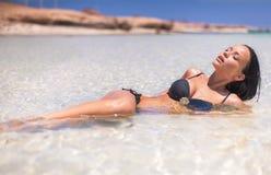 黑泳装的性感的女孩在海 图库摄影