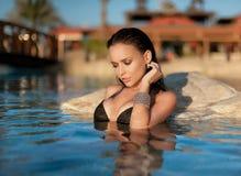 黑泳装的性感的女孩在海 库存图片