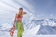 泳装的挡雪板女孩走在它上面山的 免版税库存图片