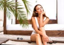 泳装的时尚女孩坐在热带棕榈的海滩 免版税库存照片